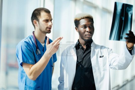 Two mixed race male doctors examining x-ray on modern office of hospital