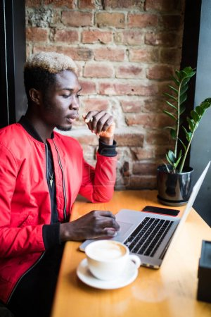 Portrait of smiling african business man working on laptop at cafe with cup of coffee