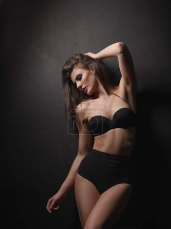 Seductive, beautiful and attractive girl with thick brown hair and sexy gorgeous body is posing in the black seamless lingerie on the dark background in the studio