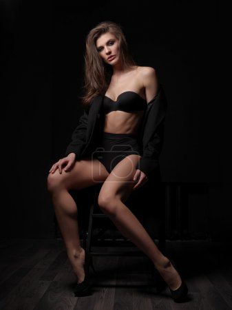 Seductive, beautiful and attractive young woman with loose brown hair, sexy gorgeous figure and long legs in the black seamless underwear and wool coat is posing on the chair in the studio