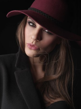 Portrait of an elegant and attractive young woman in the black wool coat, seamless underwear and marsala broad-brim hat on her head, studio photoshoot