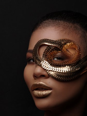 Fashion art studio portrait of an extraordinary beautiful nude african american model with perfect smooth glowing mulatto skin, make up, full golden lips, shaved haircut and gold jewelry, profile