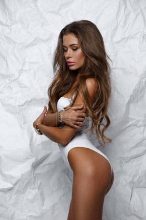 Sexy, hot and attractive girl in white seamless body underwear with slim athletic tanned figure is posing in the studio, light background