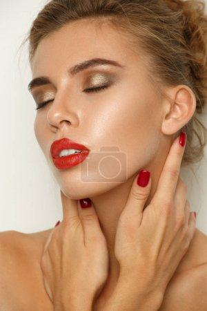 Fashionable contrasty portrait of a sexy beautiful young woman with perfect makeup (smooth glowing skin, wide groomed eyebrows, red lipstick and smokey eyes), studio shoot, light background