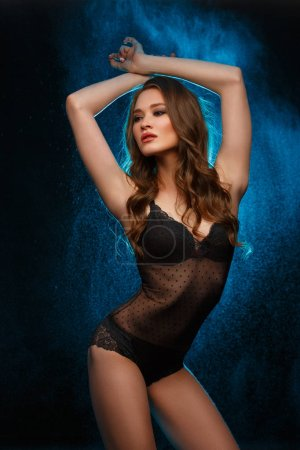 Beautiful young model in the black translucent lace body is posing in the  studio, slim attractive figure, hands up over the head. Dark background with backlight