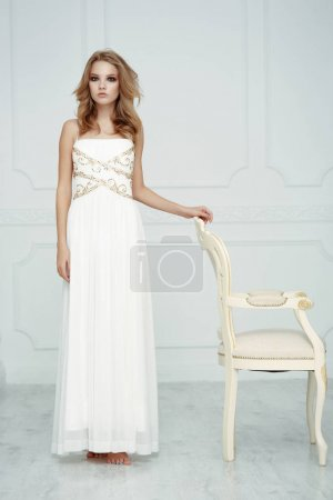 Smartly dressed gentle young beautiful girl (teenager) with frail figure and blond wavy hair wearing white evening dress embroidered with sequins is posing in the light interior studio room