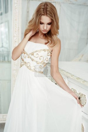Smartly dressed adorable young beautiful girl (teenager) with frail figure and blond wavy hair wearing white evening dress embroidered with sequins is posing in the light interior studio room
