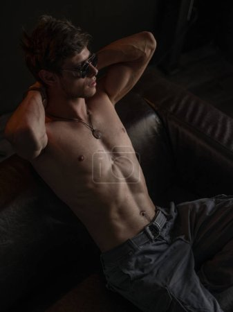 Hot, beautiful, self-confident and handsome guy with athletic body (naked torso with sexy abdominal) wearing sunglasses is posing indoors on the leather sofa