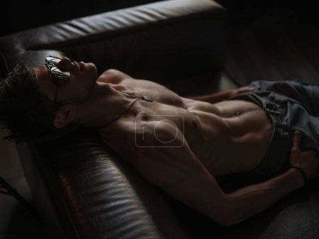 Hot, stylish, self-confident and narcissistic macho man with athletic body (naked torso with sexy abdominal) wearing sunglasses is posing indoors on the leather sofa