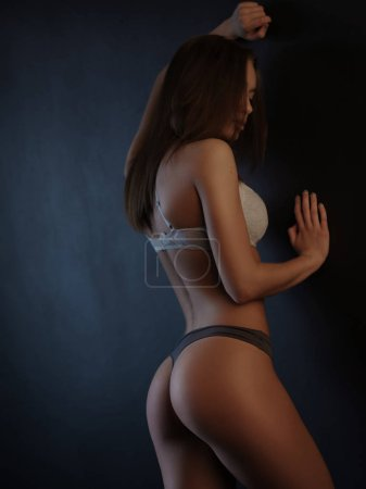 Attractive, sexy and beautiful young woman with slim seductive body (attractive buttocks) in lingerie is posing near the black wall in the studio