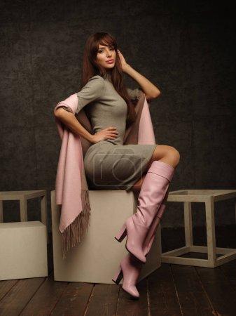 Photo pour Belle, autonome et réussie jeune femme pose vêtue d'une robe élégante, bottes roses et un foulard (tournage en studio du catalogue de vêtements à la mode, le modèle démontre la collection ) - image libre de droit