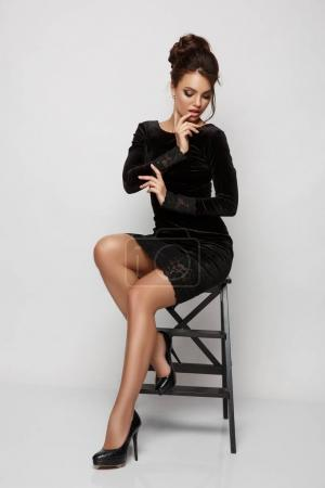 Beautiful, gorgeous and seductive young woman with makeup and hairstyle in the little sexy black dress is posing in the studio sitting on the chair, white background, fashion