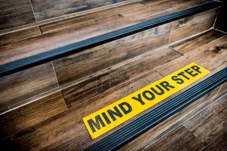 Photo pour Attention à votre autocollant étape signe collé sur escalier en bois. Avertissements, concept abstrait ou architecture d'intérieur - image libre de droit