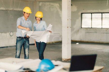 Photo pour Couple de jeunes asiatiques ingénieurs travaillant sur le plan d'action sur le chantier de construction. Génie civil, notion de rénovation industriel ou domestique. Avec l'espace de copie - image libre de droit