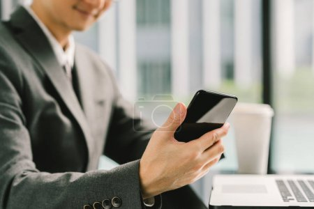 Photo for Asian businessman or entrepreneur using smartphone and laptop, working in modern office. Business communication, success, or telecommunication technology gadget concept - Royalty Free Image