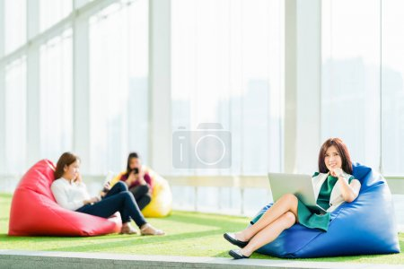 Asian students or business team sit together using laptop, digital tablet, smartphone in urban public space park. Modern casual office, Social media, wireless gadget, online shopping lifestyle concept