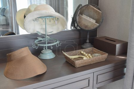 Photo for White hat and jewelry set on a dresser table in a contemporary room. - Royalty Free Image