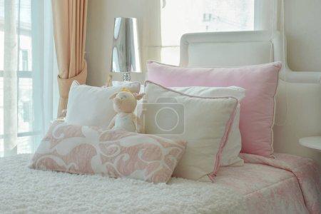 Photo pour Oreillers rose et beige sur le lit à côté de la fenêtre - image libre de droit