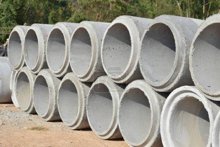 Photo pour Tuyaux de ciment empilés à la cour - image libre de droit