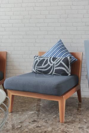 Photo pour Chaise rembourrée bleu foncé avec oreillers dans le salon - image libre de droit