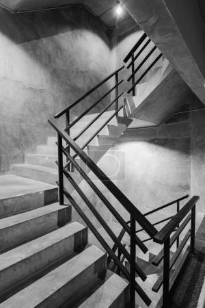 Photo pour Escalier en béton brut moderne vide avec main courante en acier noir - image libre de droit