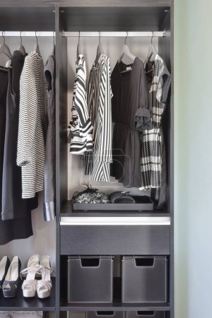 Photo for Modern closet with row of black dress and shoes in wardrobe. - Royalty Free Image