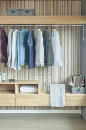 Photo for Shirts and jackets hanging in wardrobe - Royalty Free Image