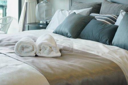 Photo pour Serviettes blanches sur le lit dans l'intérieur de la chambre élégante - image libre de droit