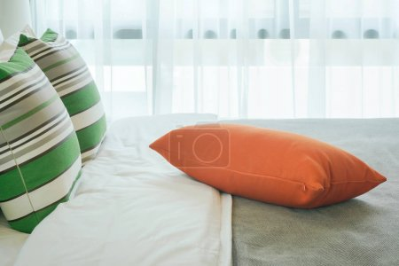 Orange pillow at center of bed in bedroom