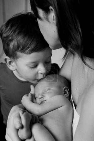 woman kissing her son and newborn baby