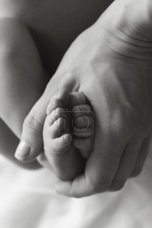 mothers hands holds baby legs