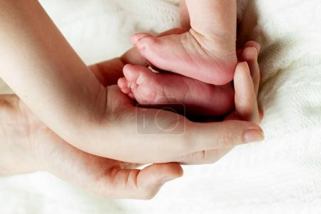 Photo for Parents  keeps the baby's feet ,close up - Royalty Free Image