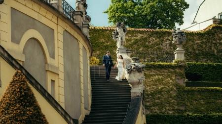 Close-up view of the cheerful newlyweds holding hands while going down the stairs. The old building is overgrown with green herbs.