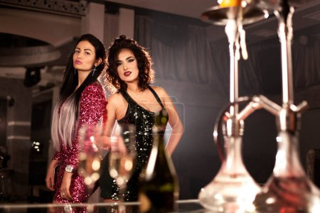 Charming girls in beautiful dresses posing for camera in hookah bar or a restaurant. Hookahs placed on a table.