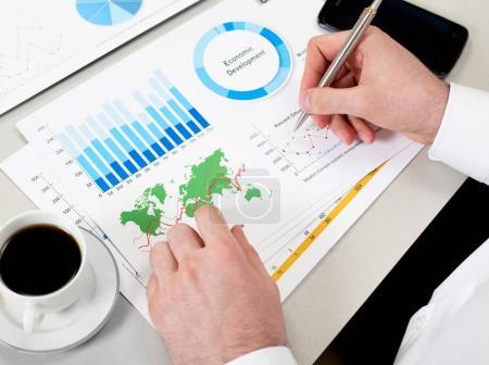 Photo pour Homme d'affaires au bureau avec papiers et ordinateur portable - image libre de droit
