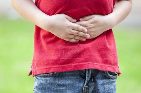 Photo pour Garçon tenant ses mains sur son ventre comme si ça faisait mal. Mauvais mal d'estomac. - image libre de droit
