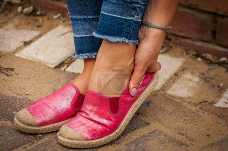 Photo pour Jeune femelle toucher son pied frotté. Nouvelles chaussures causent la peau endolorie à pied, problème de frottement pied boursouflure, cals stock image. - image libre de droit