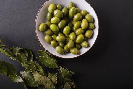 Green olives in a white bowl on a black background. Background of olives. Background with green olives. Olives. Bay leaf.