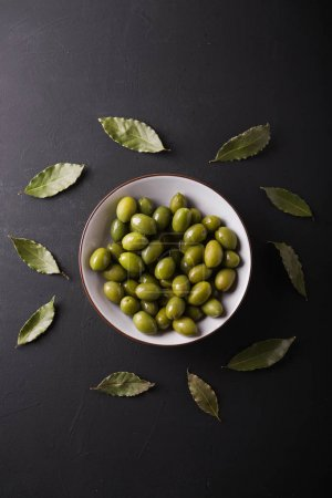 Green olives in a white bowl on a black background. Background of olives. Background with green olives. Olives. Bay leaf.