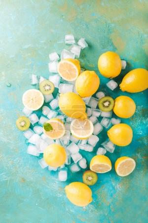 Photo for Fruits and ice cubes on turquoise background, top view - Royalty Free Image