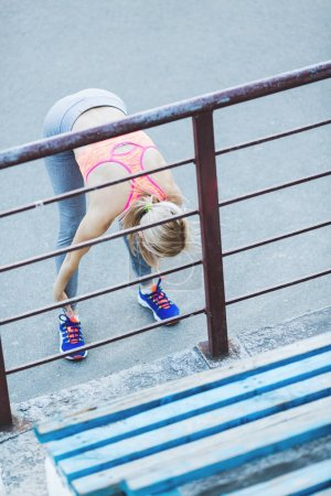 Young woman stretching before running outdoors. Fitness young woman stretching outdoors