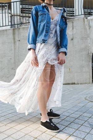 Stylish look. Bared leg. Denim jacket.  A stylish brunette woman