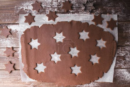 Baking Christmas cookies. Roll out the dough to cut out stars on a wooden background