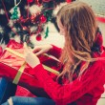 Beautiful teenage girl opening her christmas prese...