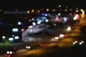 View of the city and the road from a height. Blurred cars traffic in city.