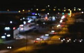 Blurred view of the city and the road from a height. Blurred cars traffic in city. Winter night.