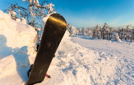 snowboard in a snowdrift on the background of a winter mountain landscape