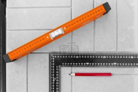 Photo pour Niveau du bâtiment sur le fond des travaux sur la pose de dalles de pavage - image libre de droit