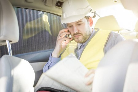 Male construction engineer in white helmet, shirt and yellow waistcoat sits in the car and scans documents while talking on the phone