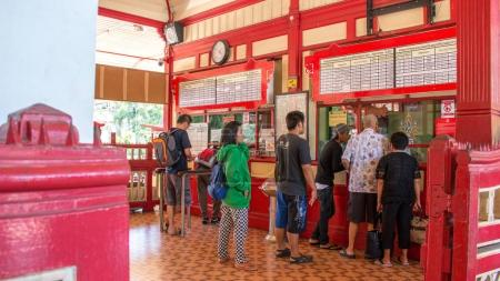 Hua Hin, Thailand - April 01,2017: Local people and tourist waiting in line for buying train ticket at train ticket counter at Hua Hin to go to Bangkok, Thailand on 1 April 2017.